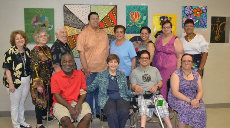 A group of artists from AHRC Nassau's East Meadow Art Gallery pose in front of their art at a local library.