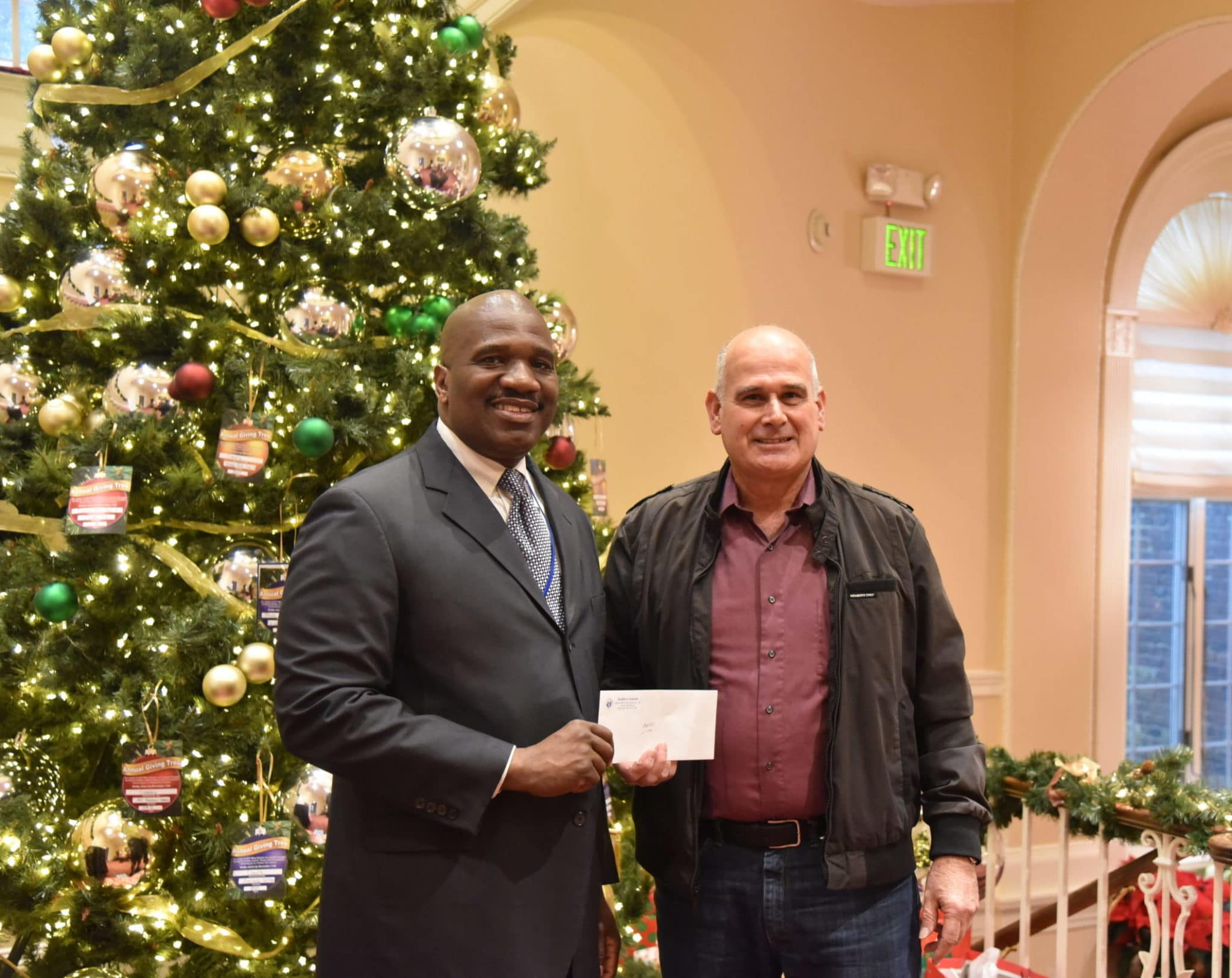 Knights of Columbus' Richie Alois presents check to Executive Director Stanfort Perry