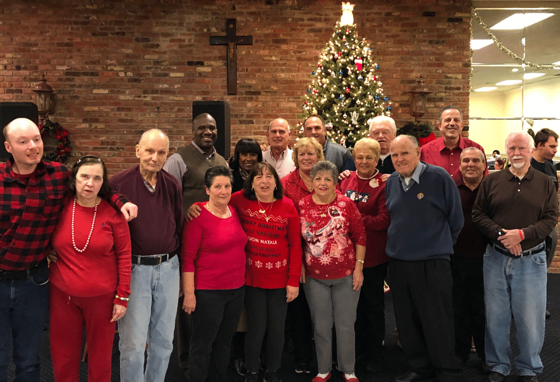 Guests of the Annual Knights of Columbus holiday party gather around the Christmas tree for a photo