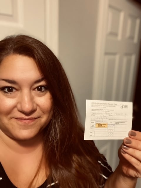 Nicole Uterano Ferrar shows vaccination card
