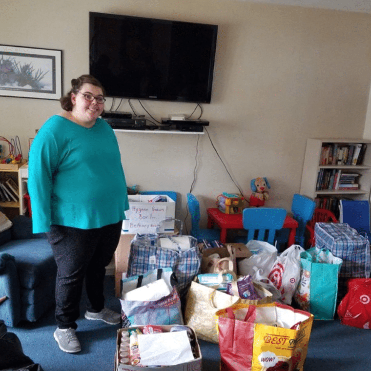 Amanda Brosnan stands next to bags of donations to support Bethany House, a local non-profit