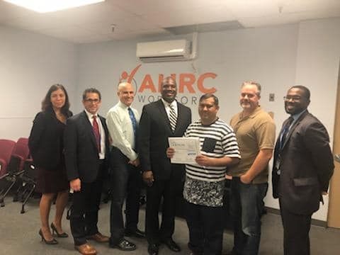 Abrar Butt is recognized by NYSID for employment excellence. He is pictured with AHRC Nassau Executive Director Stanfort Perry and other staff from the AHRC Nassau team.