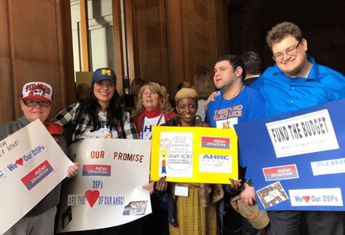 Group of self-advocates smile in Albany while rallying for #bFair2DirectCare