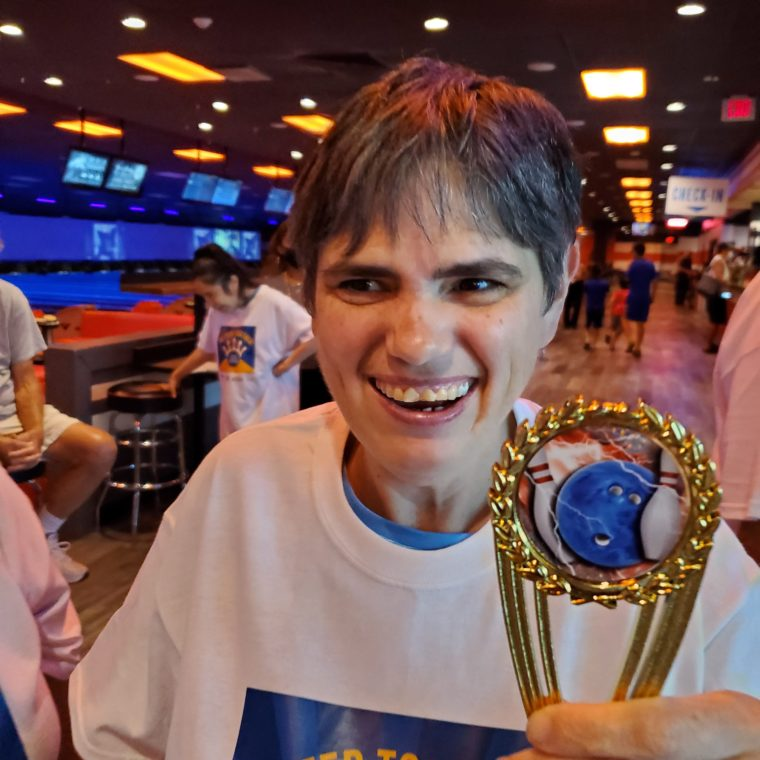 Event attendees hold participation trophies