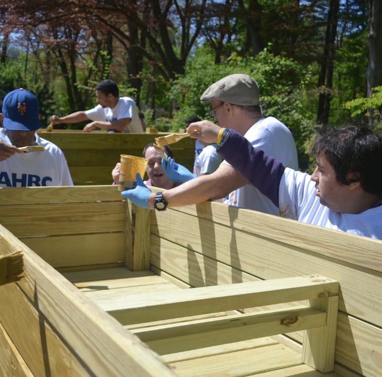 Nassau BOCES students and AHRC Nassau Day Hab participants add finish to a planter.