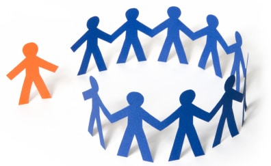 Picture of a group of blue paper dolls standing in a circle holding hands with one orange person stnding on the outside
