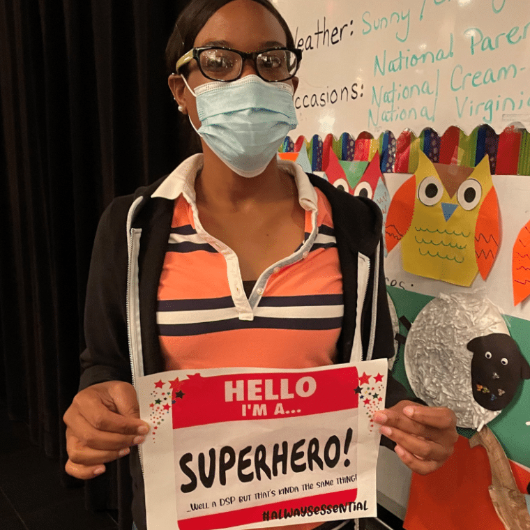 Irlande Elius, DSP, holds a sign celebrating DSP Week and her role as a superhero.