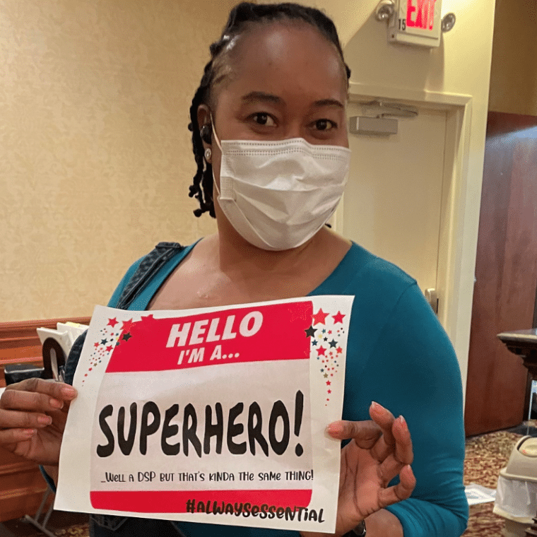 Jody Hall, DSP, holds a sign celebrating DSP Week and her role as a superhero.